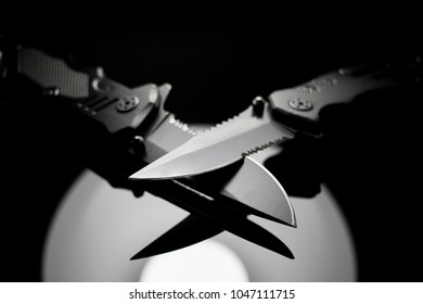 Two knives with blades touching. Black serrated weapons isolated on black background. Tactical Knife.