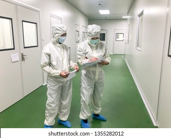 Two of Lab workers wear cleaned uniform with mask talk to the plan of the work in the corridor of pharmaceutical production plant