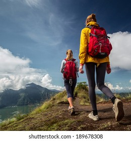 Two ladies with backpacks walking on top of the mountain at sunny day