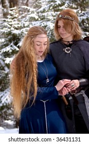 Two ladies in medieval dresses in winter forest