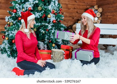 Two ladies sitting on the carpet near Christmas tree offer each other presents.