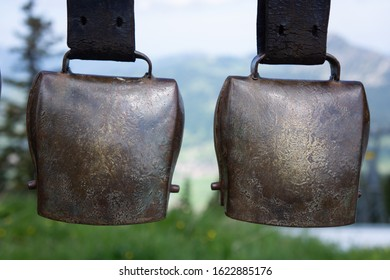 two large brass-colored cowbells were hung up. In the background you can see a mountain landscape
