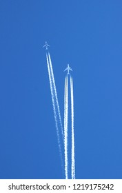 two large commercial aircrafts in the sky, condensation trails crossing each other