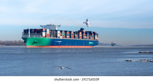 Two large Container ships leaving the port of Hamburg on the river Elbe, Germany. Ice floe on the river and seagulls in the air.