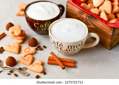 two large cups of coffee  and cookies in the form of hearts . romantic breakfast, romantic Valentine day. selective focus. on the сup description in French(mocha coffee, coffee with milk)