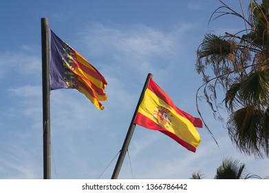 Two large flags of the Spanish state and the Valencian community on a sunny day next to the beach and the royal marina in the port of Valencia.