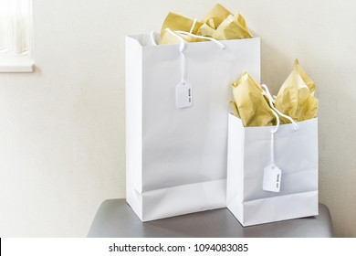 Two large gift bags with thank you note text tags on chair table in room isolated, golden yellow wrapping paper by window wall closeup