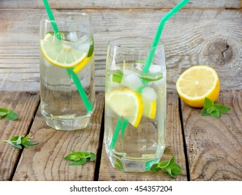 two large glass of cold lemonade with ice, lemon, mint leaves and straw.