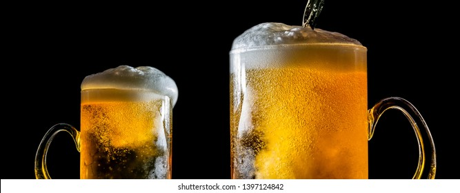 Two large glasses of beer with foam close-up, facing each other, isolated against a black background. Two overflowing glasses of beer with flowing foam. Beer is pouring into a glass.