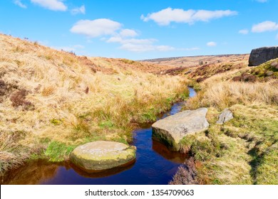 Two large gritstone stepping stones across the narrow, deep, water of Burbage Brook in the Derbyshire Peak District.