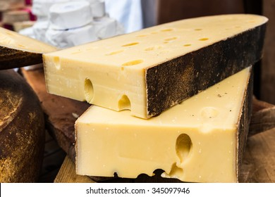Two large pieces of Emmental cheese  on the wooden table