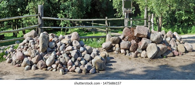 Two large piles of granite boulders and stones lie in forest near a village fence