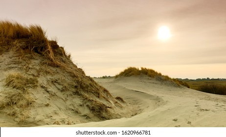 Two large sandy dunes, the sun on pastel colored sky and the roof of a house in the distance.