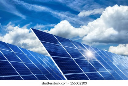 Two large solar panels under the blue sky with lively clouds, reflecting the sun