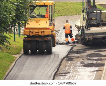 Two large steamrollers laying of asphalt in city Park, industrial machinery - asphalt roller on summer day, development of the road, worker people