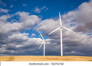 Two large wind turbines in a golden field with a small road or trail leading through the left side