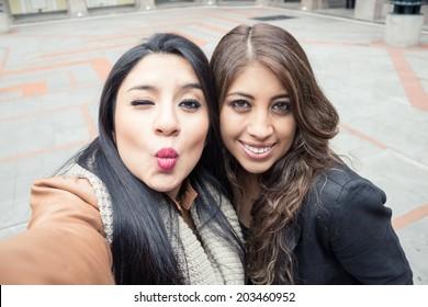 two latin girls taking a selfie outdoors