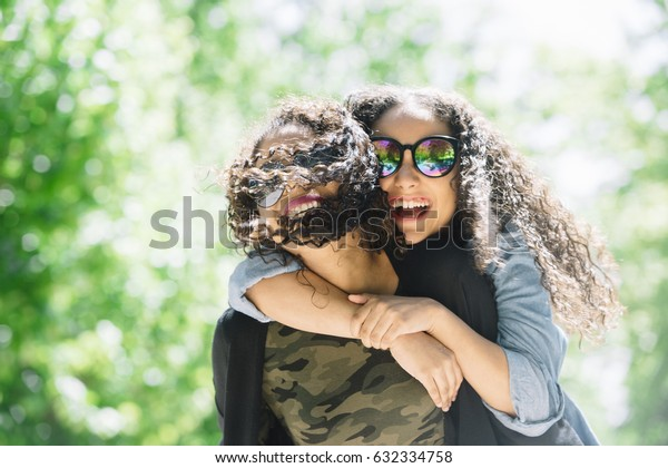 Two latin race friends dancing and having fun outdoors