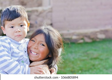 Two latin siblings hugging outside.
