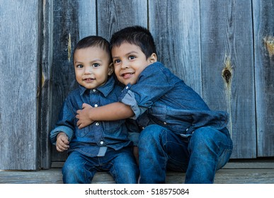 Two latino children hugging on a staircase