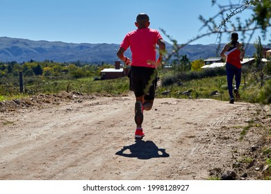 Two latino man running a race on a rural road during summer. Crosscountry race. Copy space.
