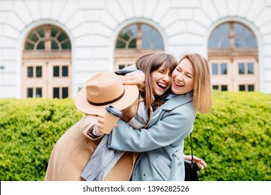 Two laughing candide hipster blond women in trendy clothes. Female posing on street background. Female showing positive face emotions. Lifestyle concept.