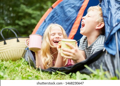 Two laughing children in the summer holidays camping in tent with cups