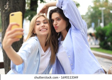 Two laughing friends enjoying weekend together and making selfie on city background.