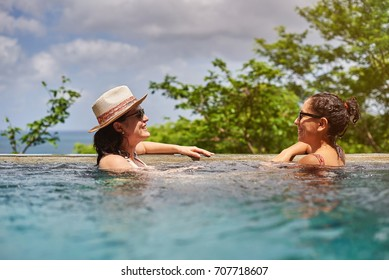 Two laughing girl in pool on sunny bright day
