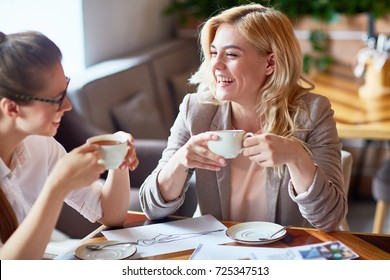 Two laughing girls having tea and discussing new creative project in cafe