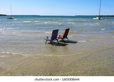 Two lawn chairs standing in water on a sandy beach with sail boats in the background.