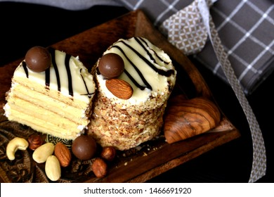 Two layered white chocolate and nuts keto desserts served on dark wooden tray, decorated with almonds and various nuts. Alternative ketogenic diet concept.
