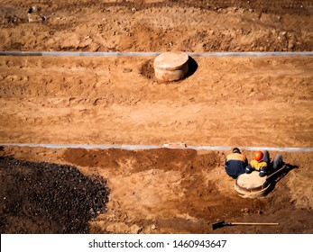 two lazy builders are sitting on a sand