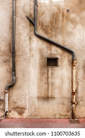 Two lead drainpipes snake down a wall in the town of Beaune at the center of the Burgundy region in France.