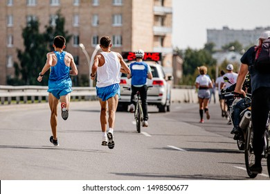 two leaders athletes runners run marathon for car escort