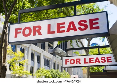 Two For Lease signs on display outside buildings during daytime