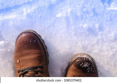 Two leather brown boots on a snow background. Top view.
