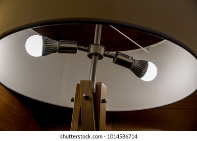 Two LED light blubs in round modern design lamp with wooden structure