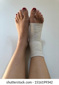 Two legs against the white wall, one ankle with elastic bandage after the sports injury - sprain of the ankle