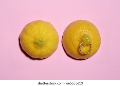 two lemon halves with ring piercing on pastel pink background