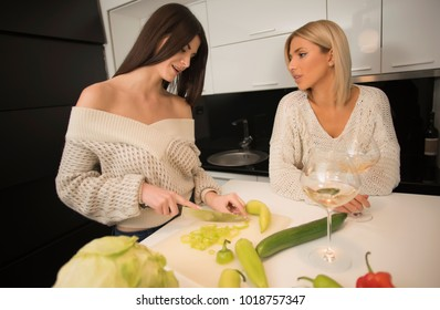 two lesbian female friends making salad in the kitchen and drinking wine from a wine glasses. life stile concept. healthy food