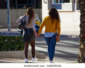Two Lesbian gay girls women holding each other hands while walking in the street