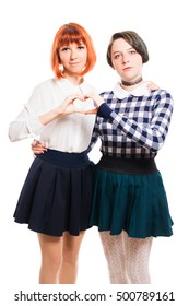 Two lesbian girls hugging and making heart from his hands. On white, isolated background.