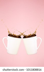 Two levitating coffee mugs with splashes. Coffee concept. Minimal art trend. Solid background. Vertical