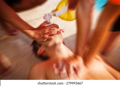 Two lifeguards giving cardiopulmonary resuscitation (CPR) to a drowned man. Zoom effect.