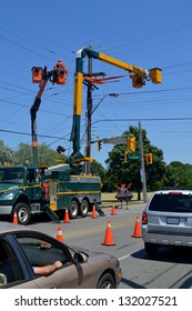 Two lift trucks from a hydro company working on power lines cutting of the traffic in Hamilton Ontario, Canada.