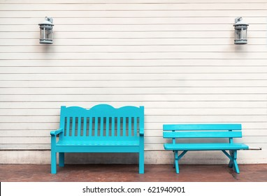 two Light blue wooden bench and wooden wall.