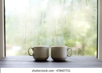 Two the light cup of coffee on a wooden table, against the window after rainy weather / cozy atmosphere for coffee breaks