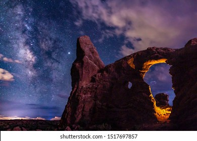 Two light sources on Turret Arch: one manmade, one mother nature, Lightning, light up Turret Arch in Arches National Park, Utah.