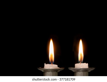 Two lighted Jewish Shabbat candles burning low and melting. Copy space. Isolated on a black background.